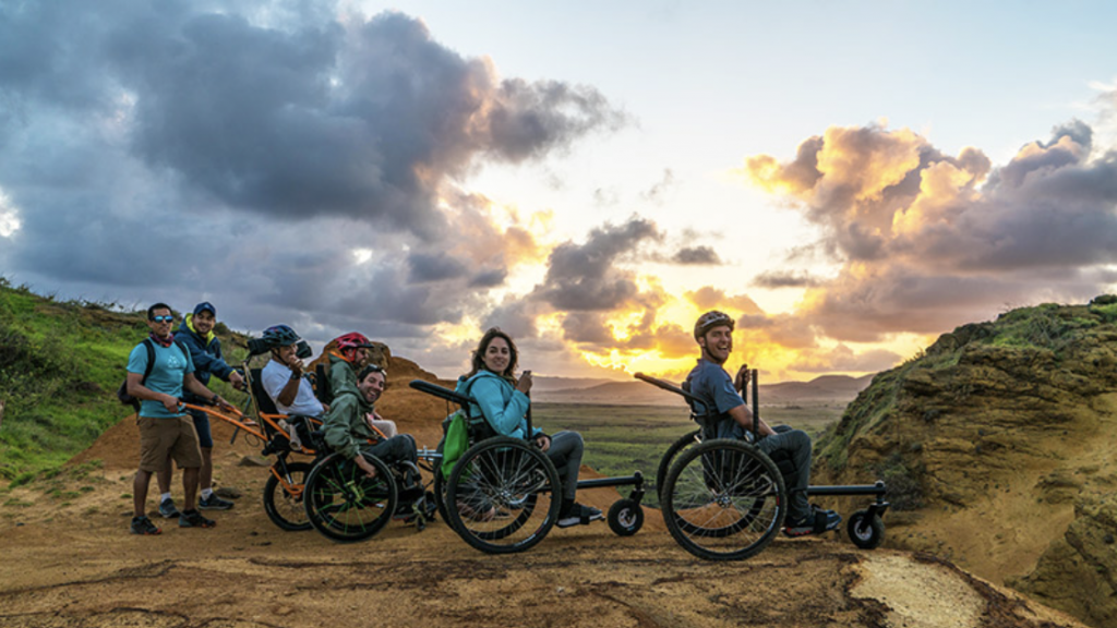 a group of people on a mountain top in wheelchairs while the sun sets behind them