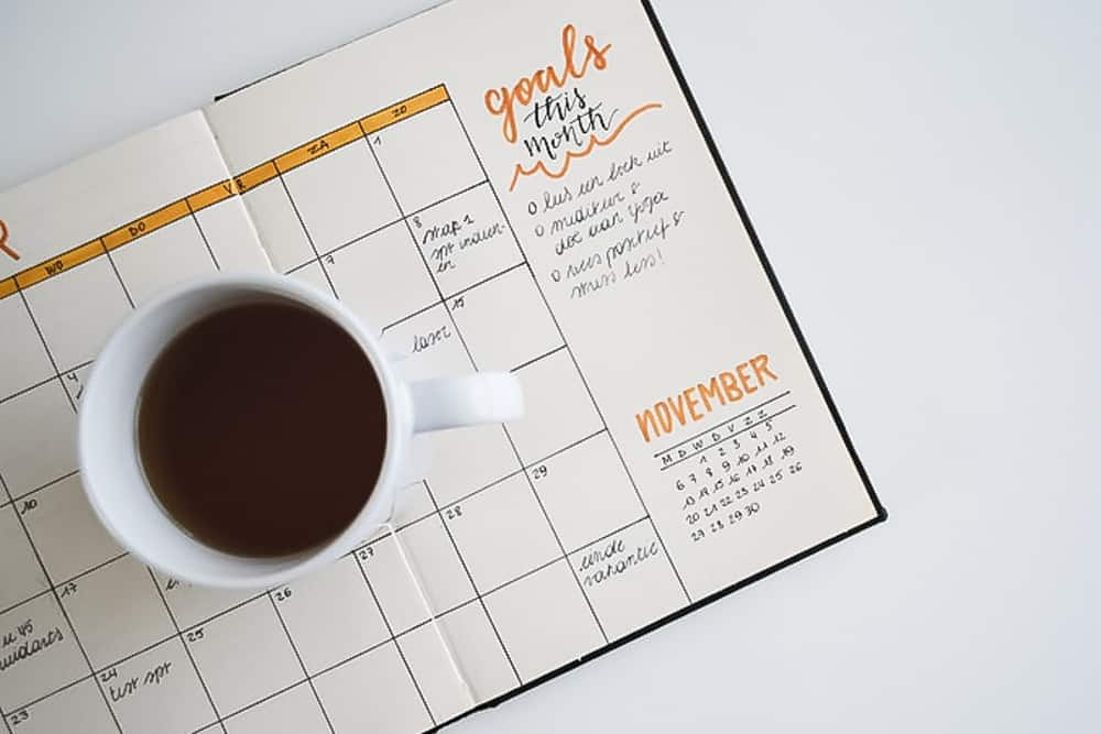 bullet journal on white desk with coffee