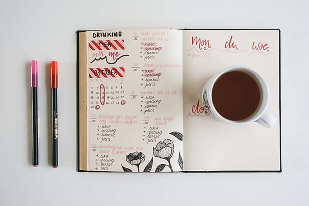bullet journal with coffee and pink pens