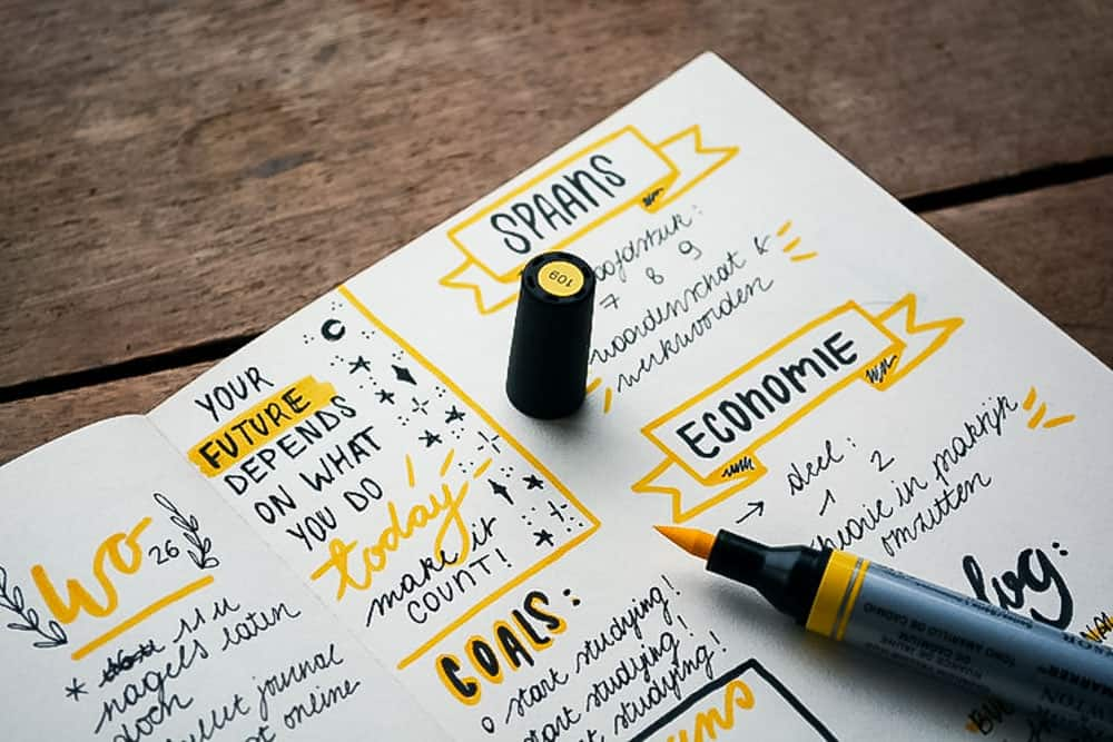 close up of bullet journal on wooden desk with yellow highlighter