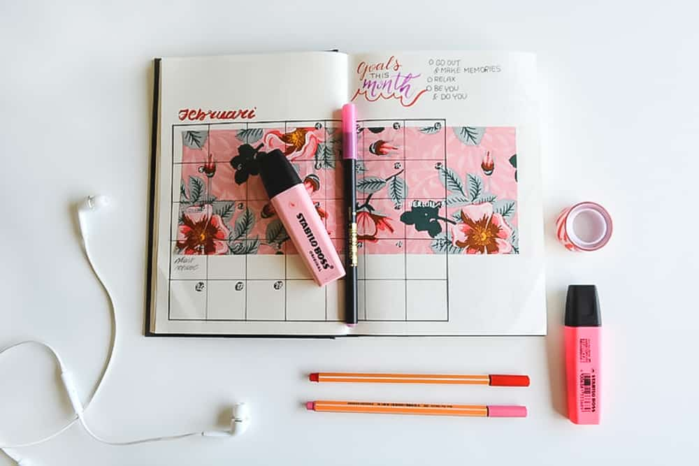 bullet journal with pink pens and earbuds and washi tape