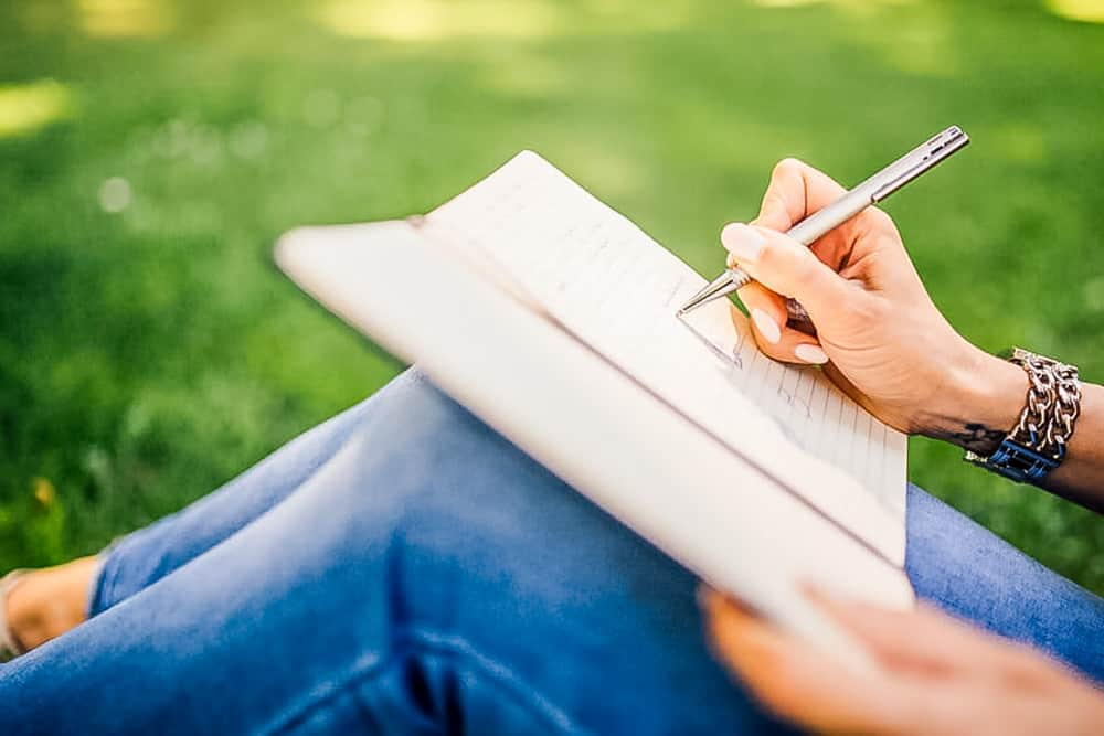 close up of woman writing in journal