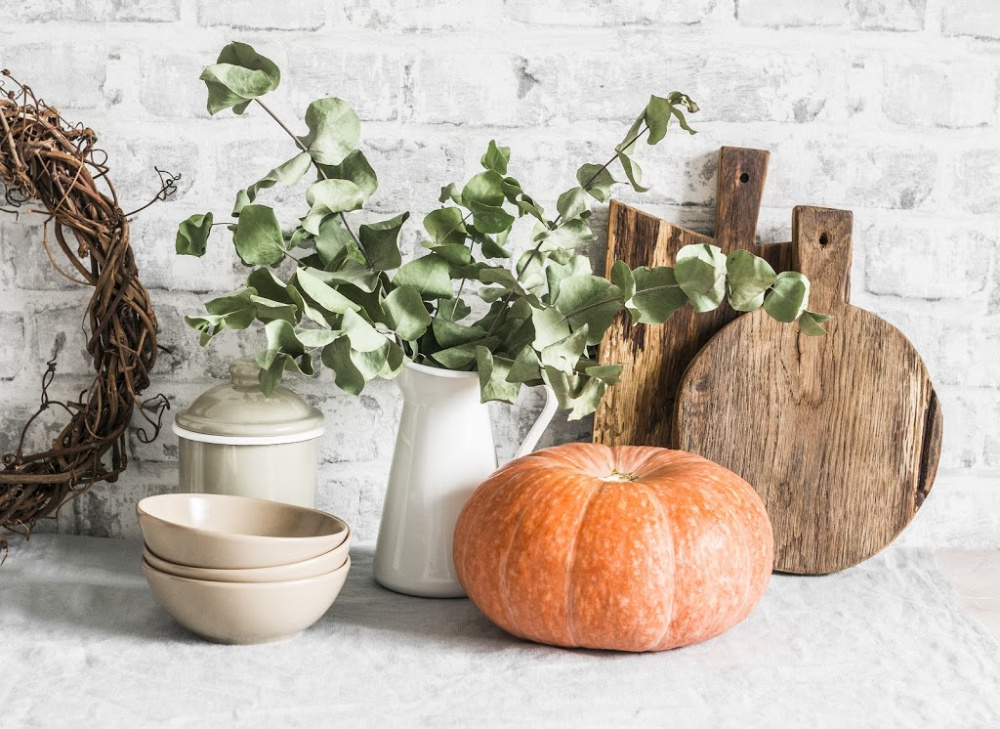 Kitchen autumn still life. Crockery, cutting boards, vine wreath, pumpkin on the table, on a light background. Rustic cozy style. Flat lay