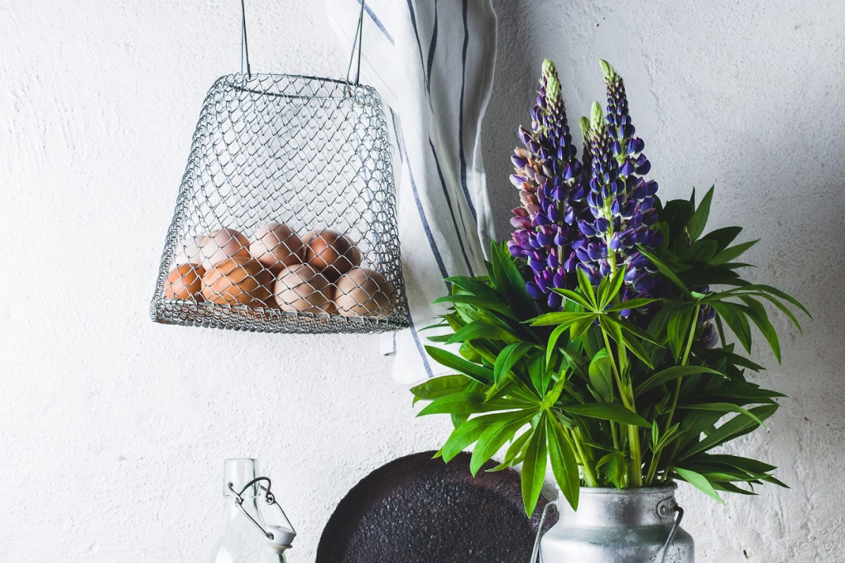 Concept of rural kitchen. Lupines in a can, milk, eggs and ware on a wooden table against the background of a white wall