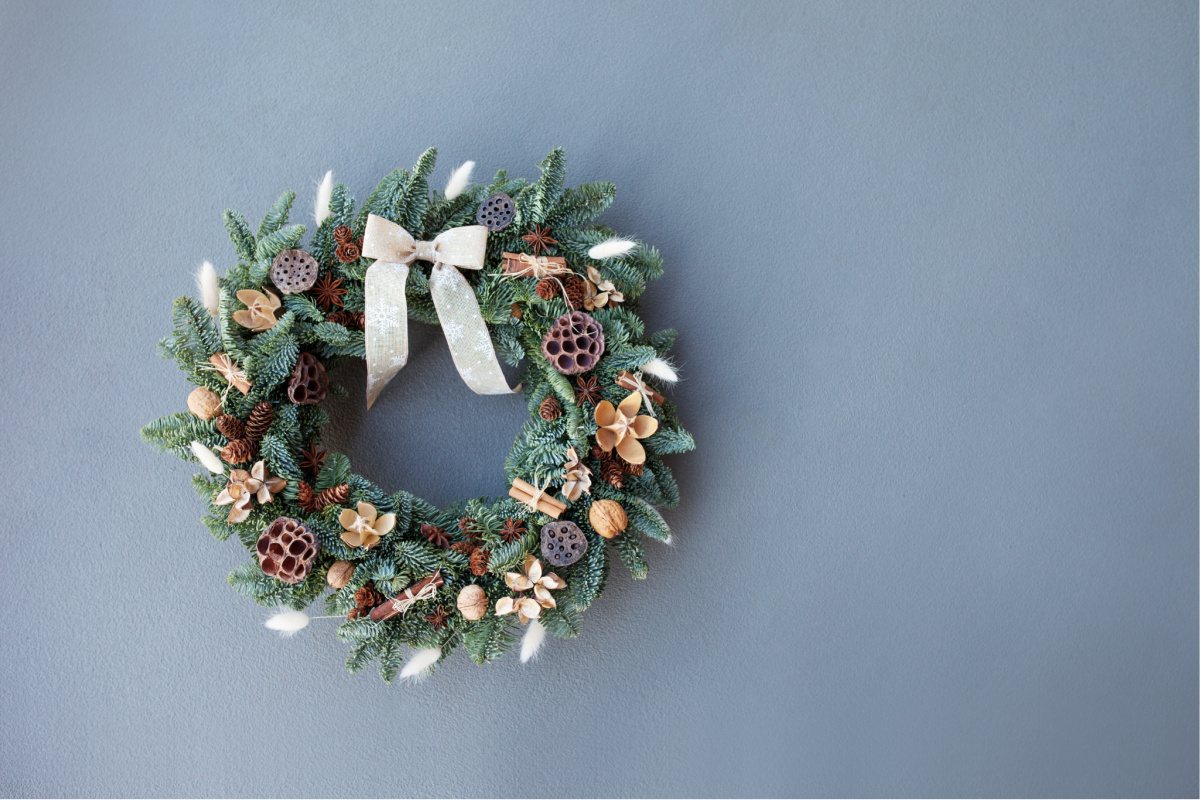 Christmas wreath made of natural fir branches  hanging on a grey wall.  Wreath with natural ornaments: bumps, walnuts, cinnamon, cones. New year and winter holidays. Christmas decor. Copy space