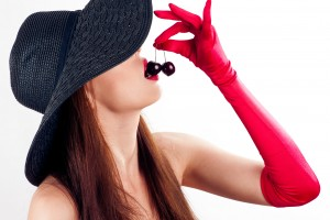 beautiful woman in hat and gloves eating cherries