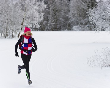 Women jogging through snowy forest.