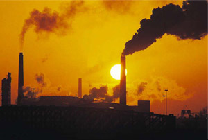 sunset shown behind high carbon emission factory