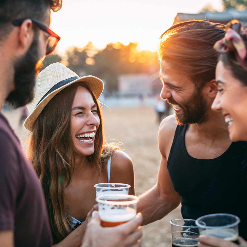 Four people laughing over drinks at sunset