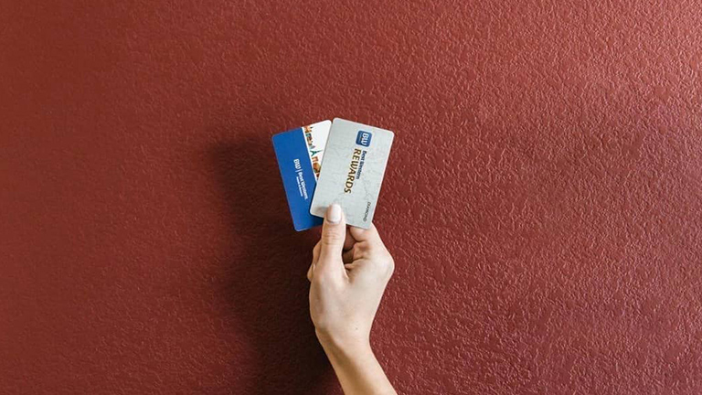 Woman holding Best Western Rewards cards against red wall