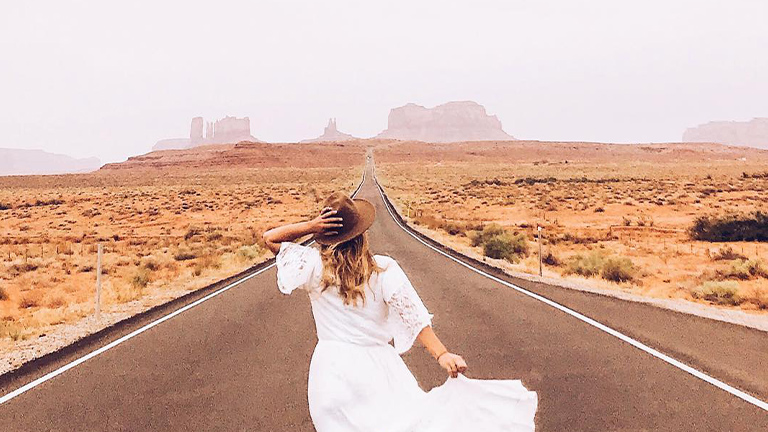 Girl in white dress with hat running on road to Monument Valley