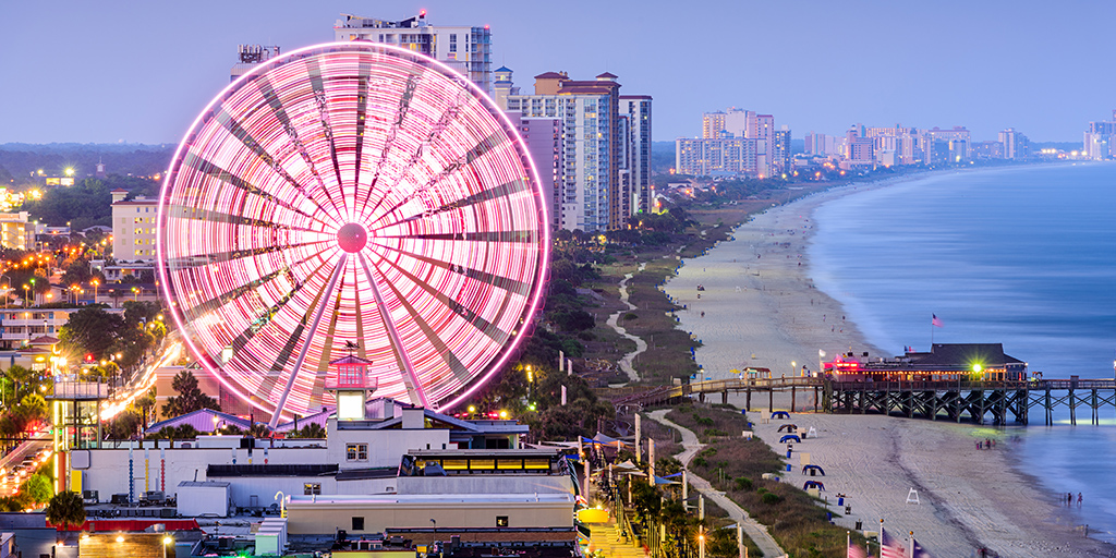 Myrtle Beach boardwalk with beach, buildings and ferris wheel