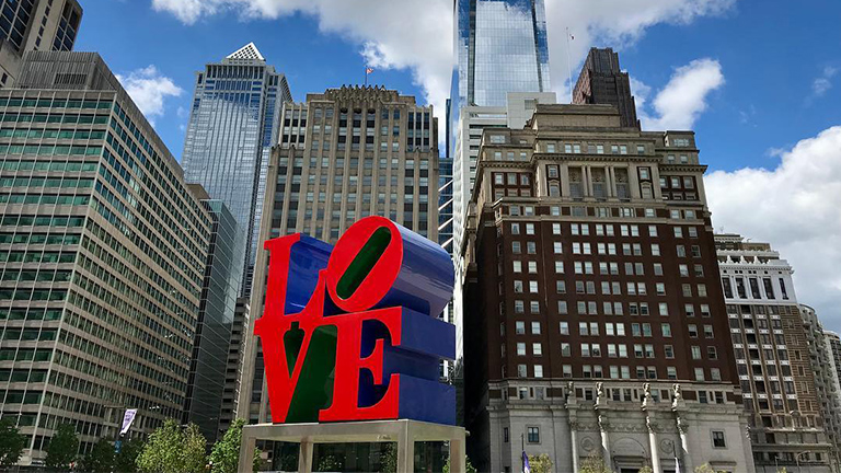 Image of LOVE Statue, by Robert Indiana, against the Philadelphia city skyline.
