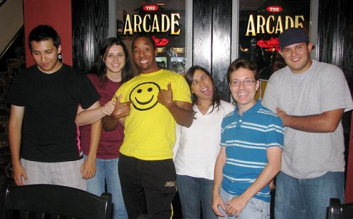 A diverse group of older teenagers (four boys and two girls), smile and make silly faces while standing in front of the arcade.