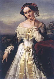 A three-quarter length portrait of a young white woman in the open air. She wears a shawl over an elaborate-long-sleeved dress that exposes her shoulders and has a hat on over her centrally-parted dark hair.