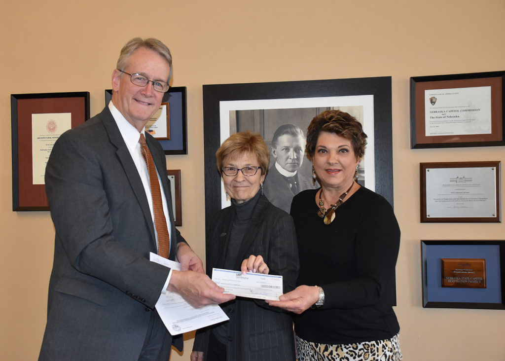 Former State Senators DiAnna Schimek and Vickie MacDonald with the Association of Former Legislators present Capitol Administrator Bob Ripley a check to begin the restoration process.