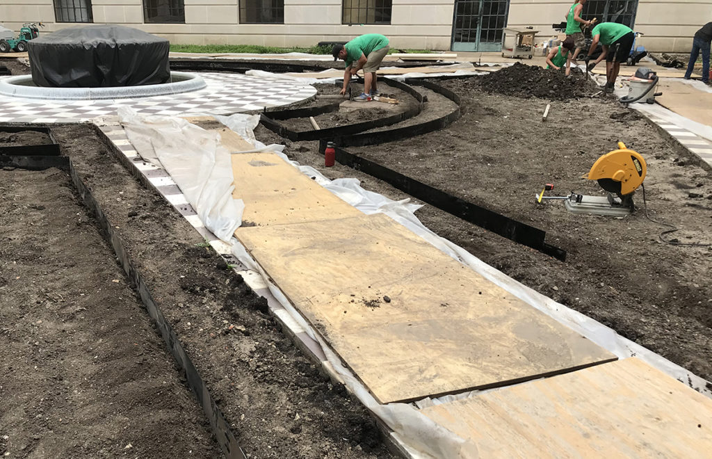 Contractors install edging outlining the planting beds