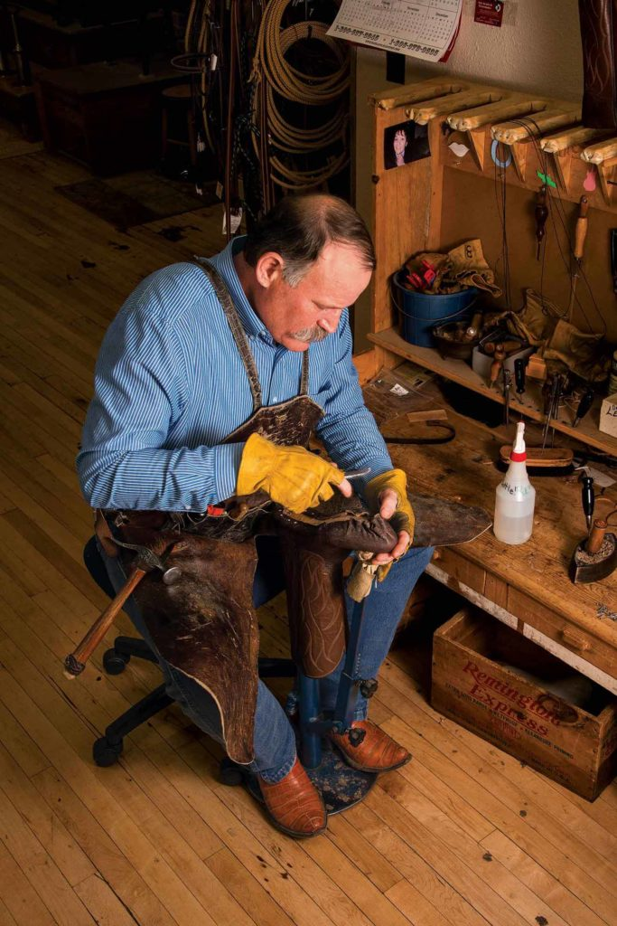 Dan uses a waxed awl to make a hole before pulling through another flax-threaded stitch.