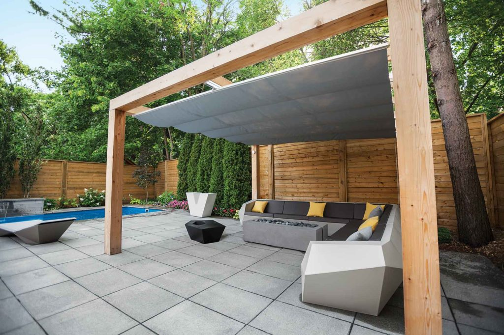 Locating a canopied pergola up against the privacy fence provides shelter from the elements.