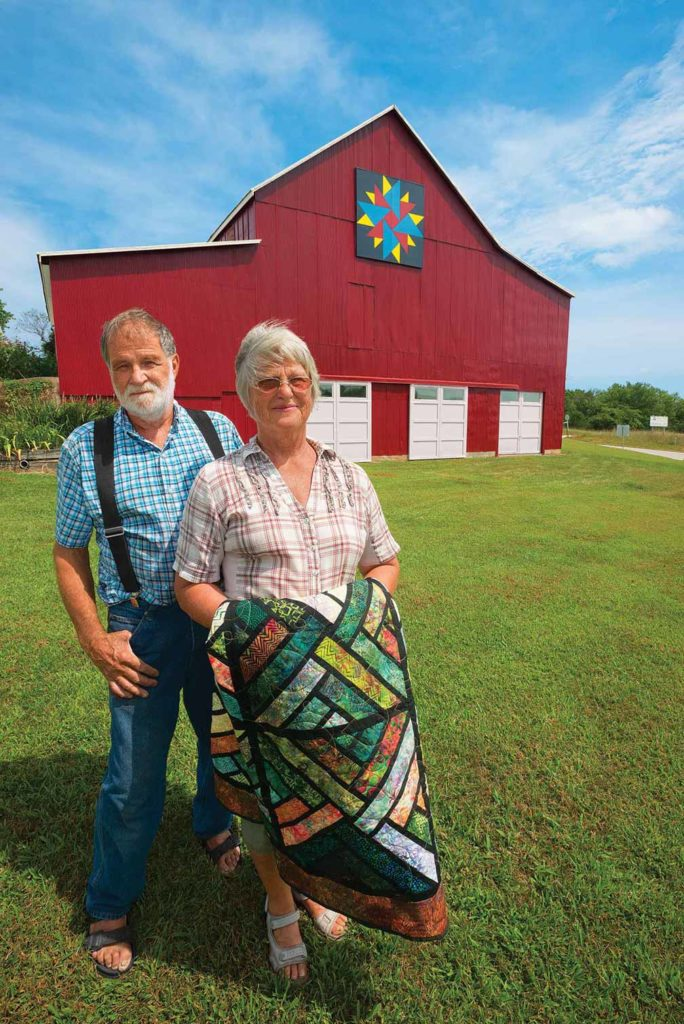 Laverne LaBoube holds one of her favorite quilts (Fractured Paintbox by Judy Niemeyer) in front of the 8x8-foot Star Variation block that husband Norbert helped add to their barn.