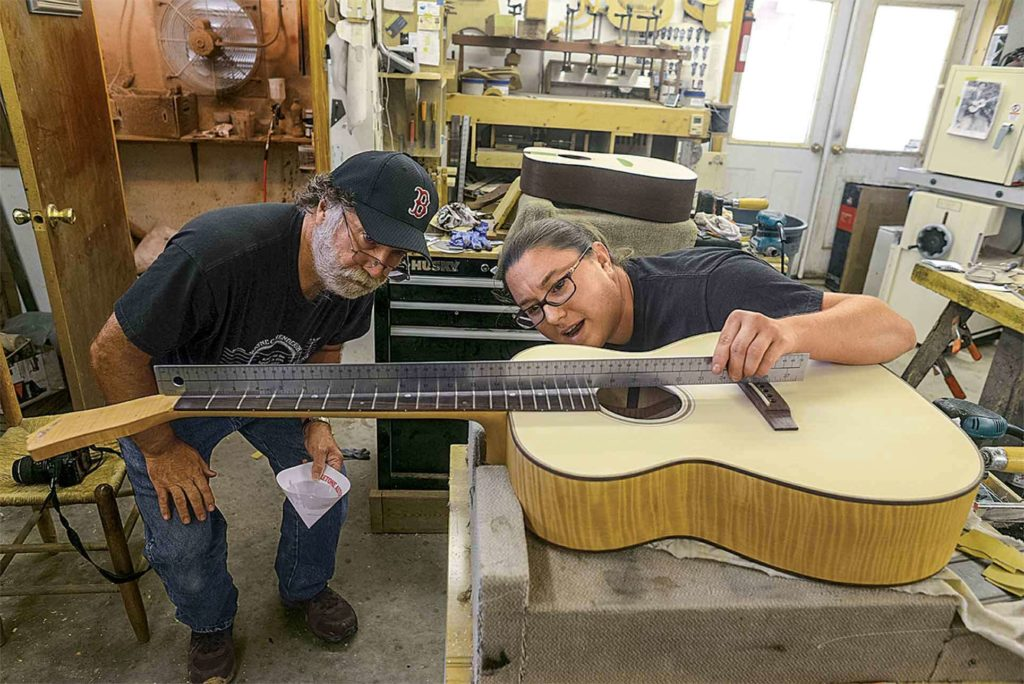 Henderson and daughter Jayne inspect one of the guitars she's building.