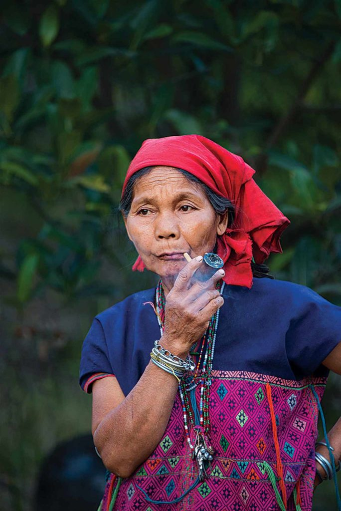A village elder enjoys an afternoon smoke of home-grown tobacco.