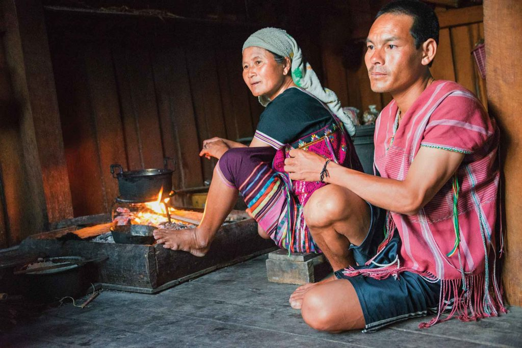 Li Chao and his wife (also called Chao) prepare for supper. A bed of sand keeps the fire pit from burning their home's wood floor.