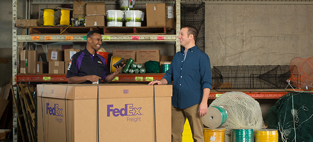 Employees in a warehouse with a FedEx Freight box