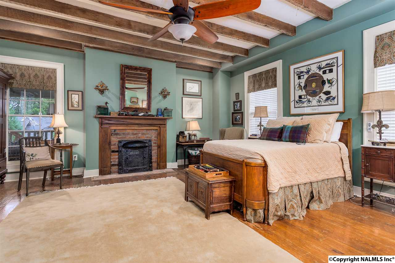 This bedroom has rough-hewn beams on the ceiling.