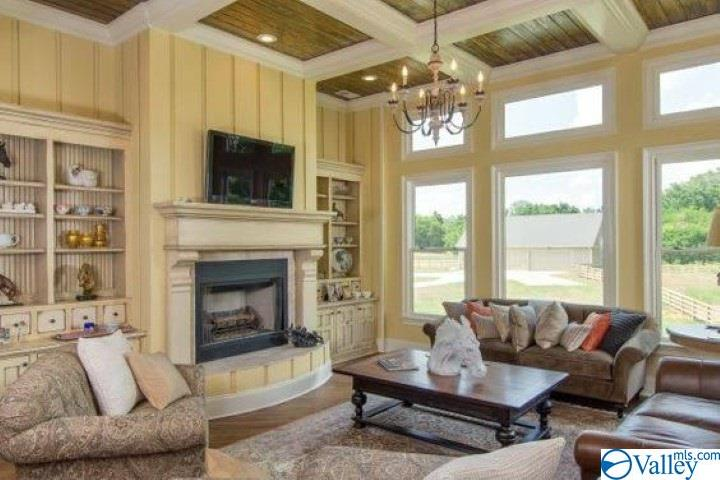 Den area with fireplace and coffered ceilings righ
