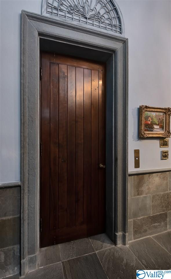 Wood paneled elevator with blue stone flooring and