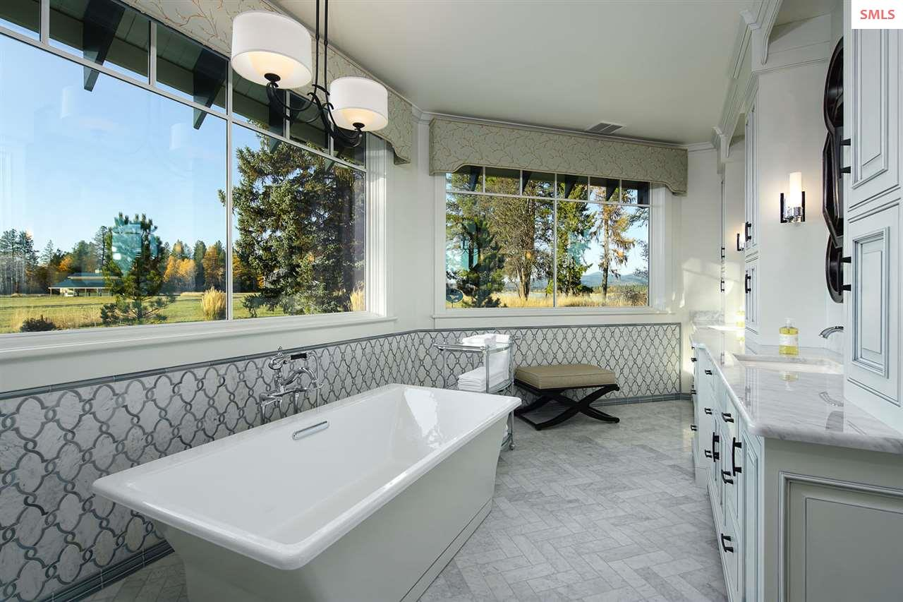 The master bath offers double sinks and a cast iro