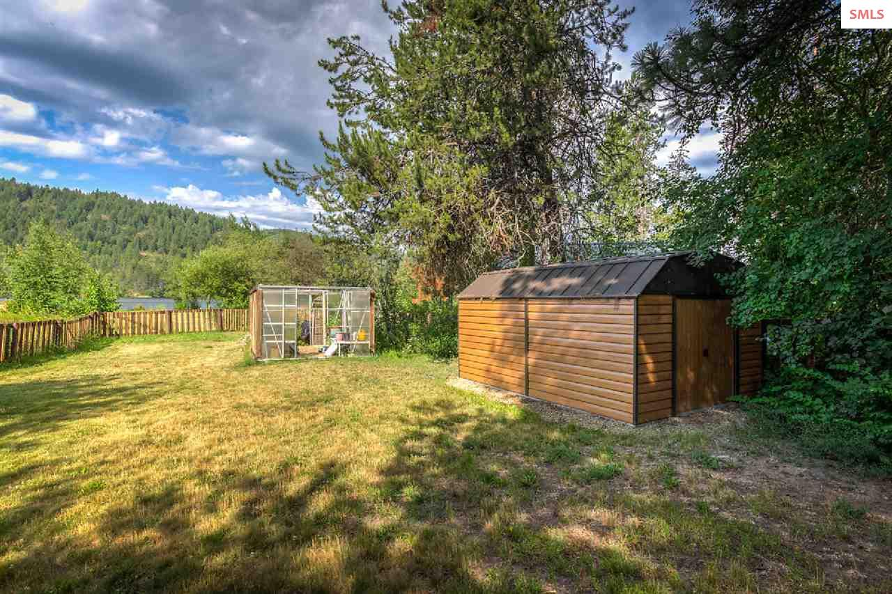A storage shed and a green house await your vision