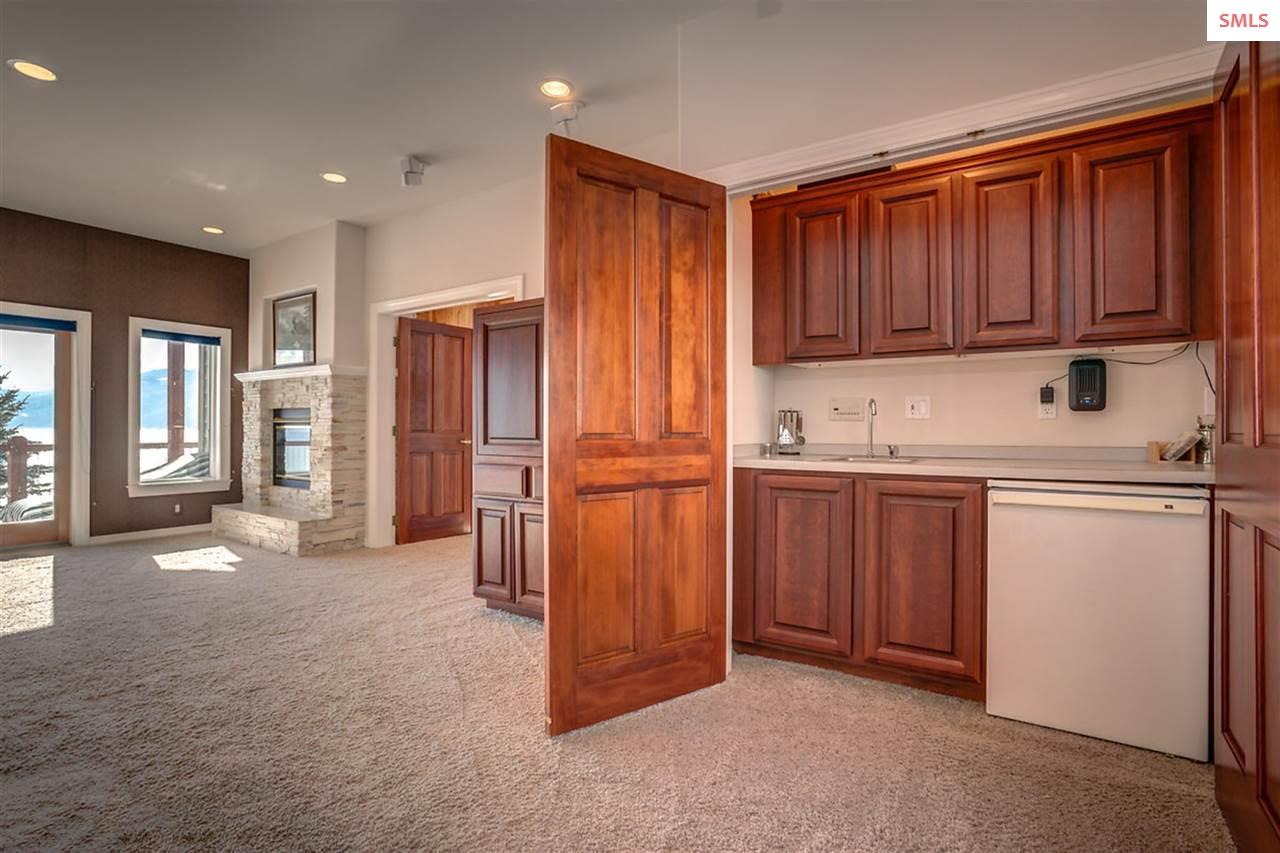 Cherry cabinets conceal a full wet bar in the libr