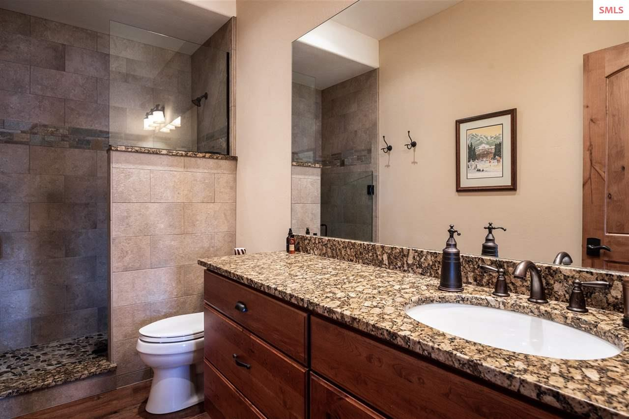 Granite, glass & tile accent this bathroom with wa
