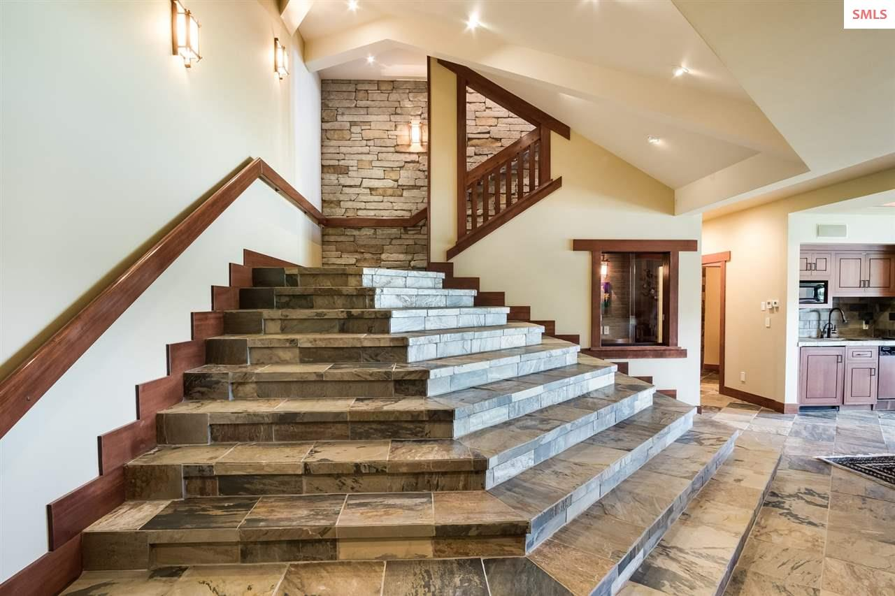 Dramatic staircase opens up to lower level family