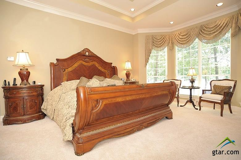 The master bedroom features tray ceiling and unbel