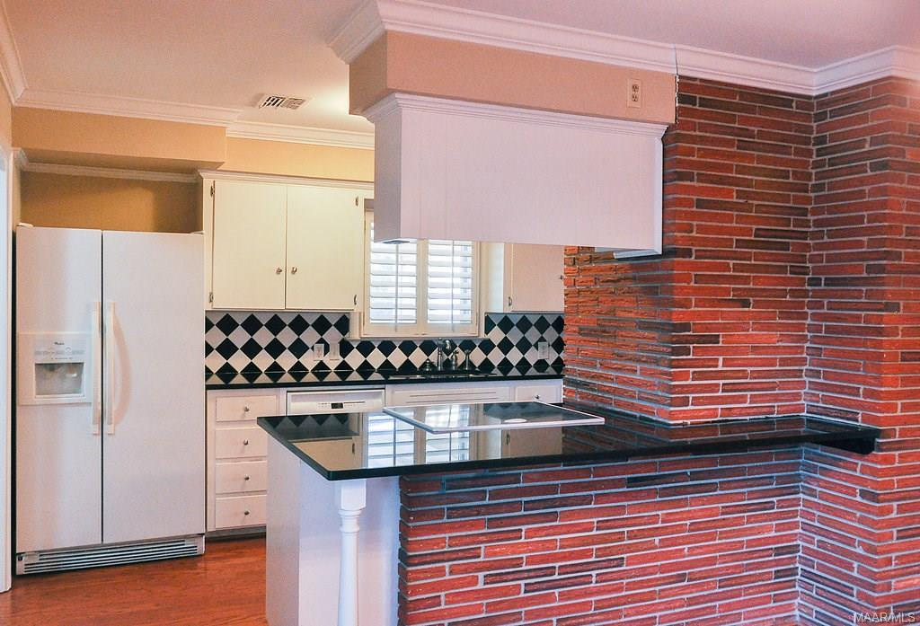 Exposed brick from the fireplace shows in the kitc