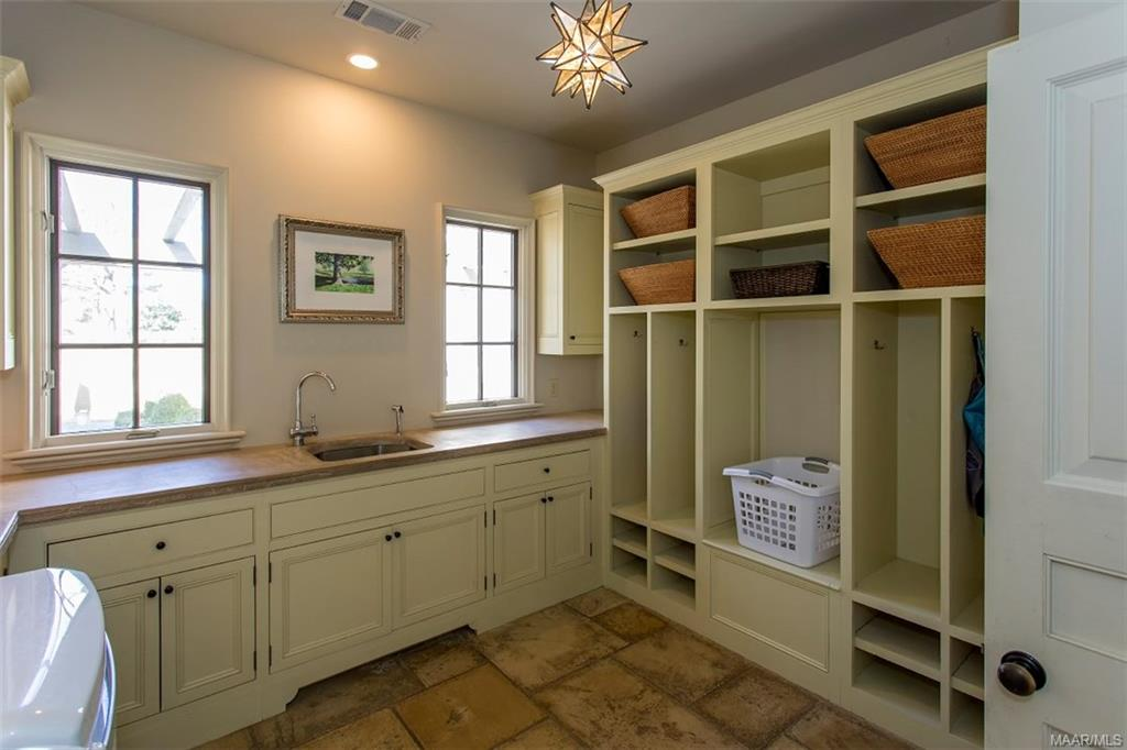 Spacious Laundry Room with Sink and Custom Cabinet