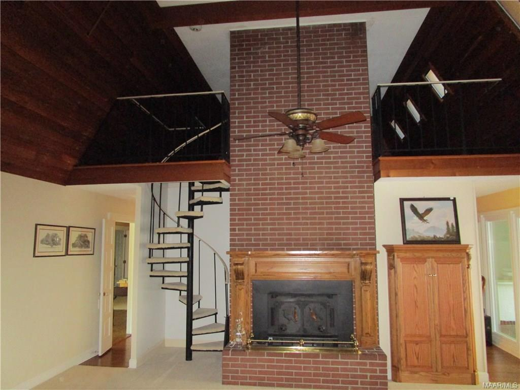 Fireplace and spiral staircase to loft area
