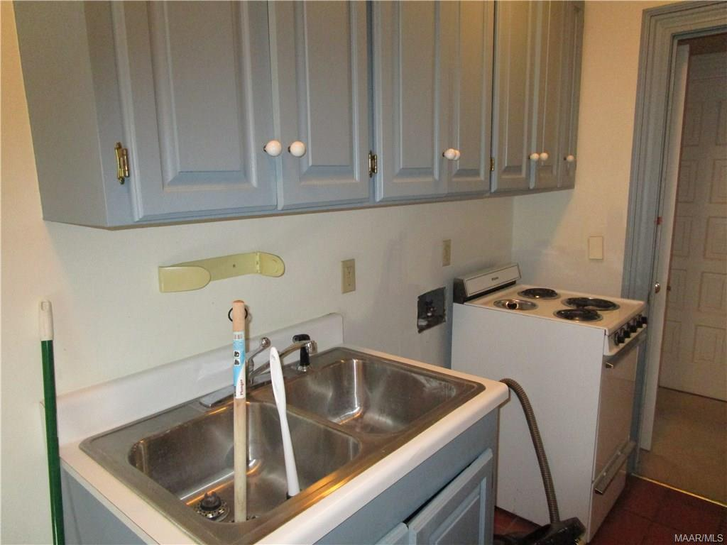 Laundry room w/more cabinets, sink and stove