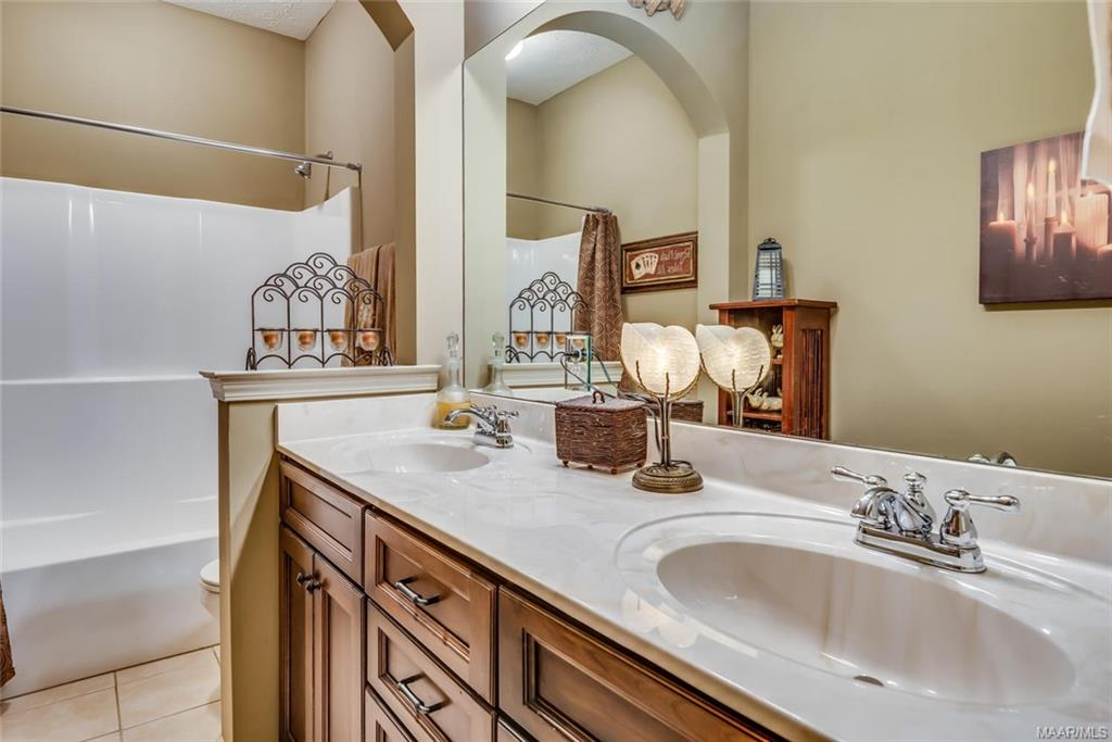 Double vanity, linen closet, and another arched op