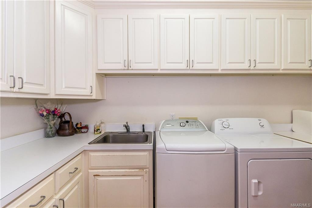 Wonderful laundry room with countertops and sink.