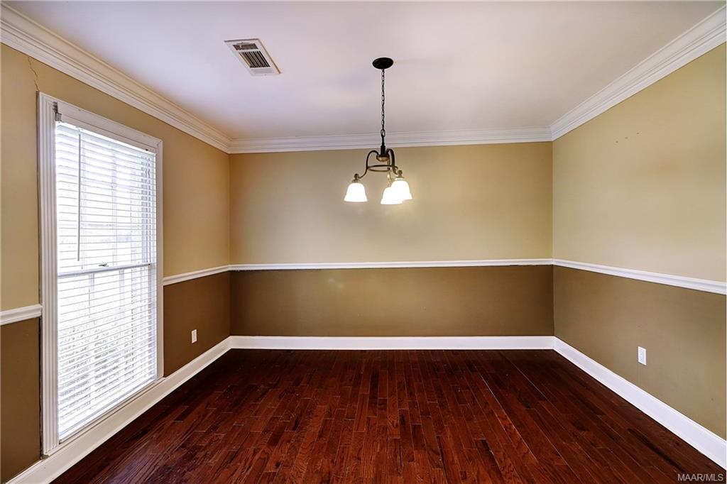 Separate dining room with chair railing and good l
