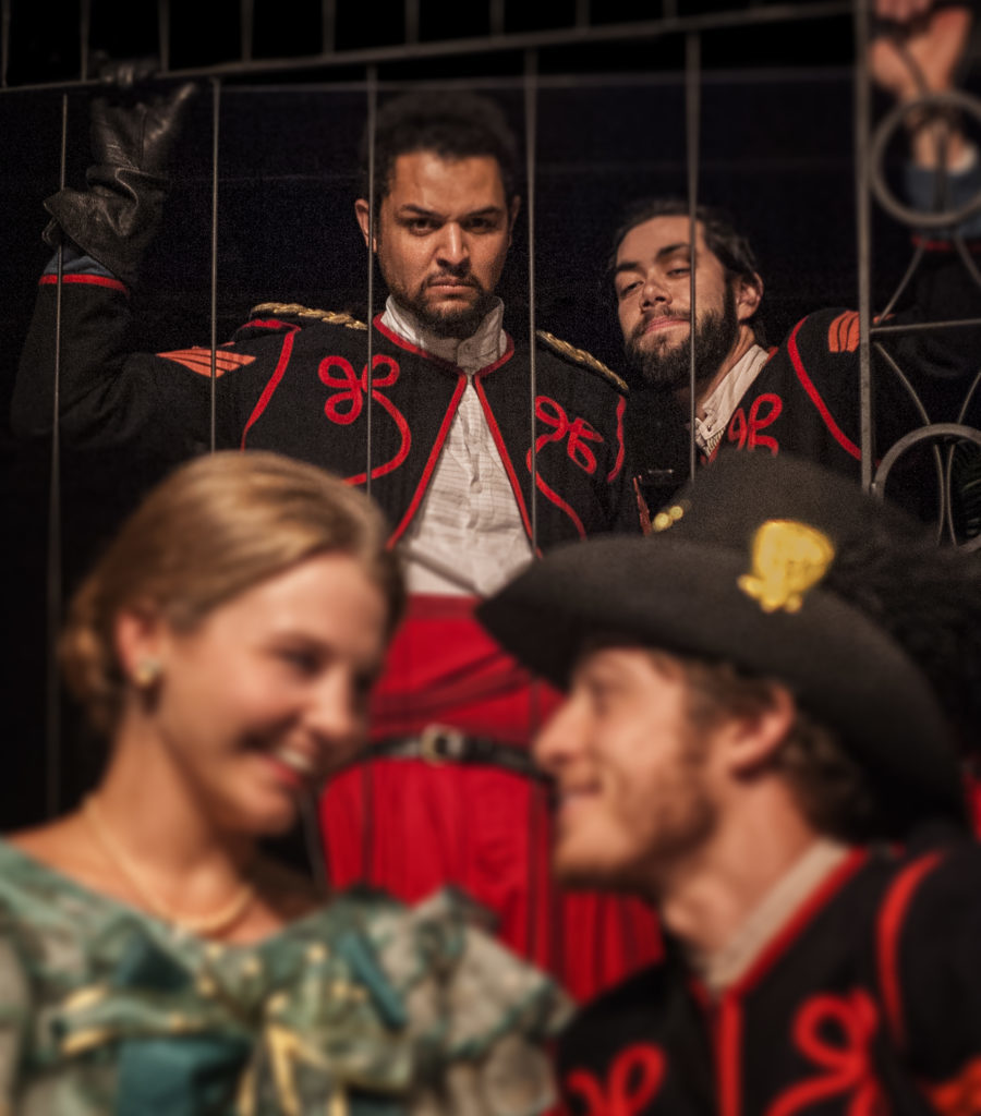 Iago (Matt Bowdren, top right) plots against Othello (Chris Okawa) & his love as he plants the idea that Desdemona (Kierna Conner) is having an affair with Cassio (Ethan Kirschbaum) in Shakespeare's OTHELLO, running March 8 – April 5, 2015 at UA Arizona Repertory Theatre in the Tornabene Theatre (Photo by Ed Flores).