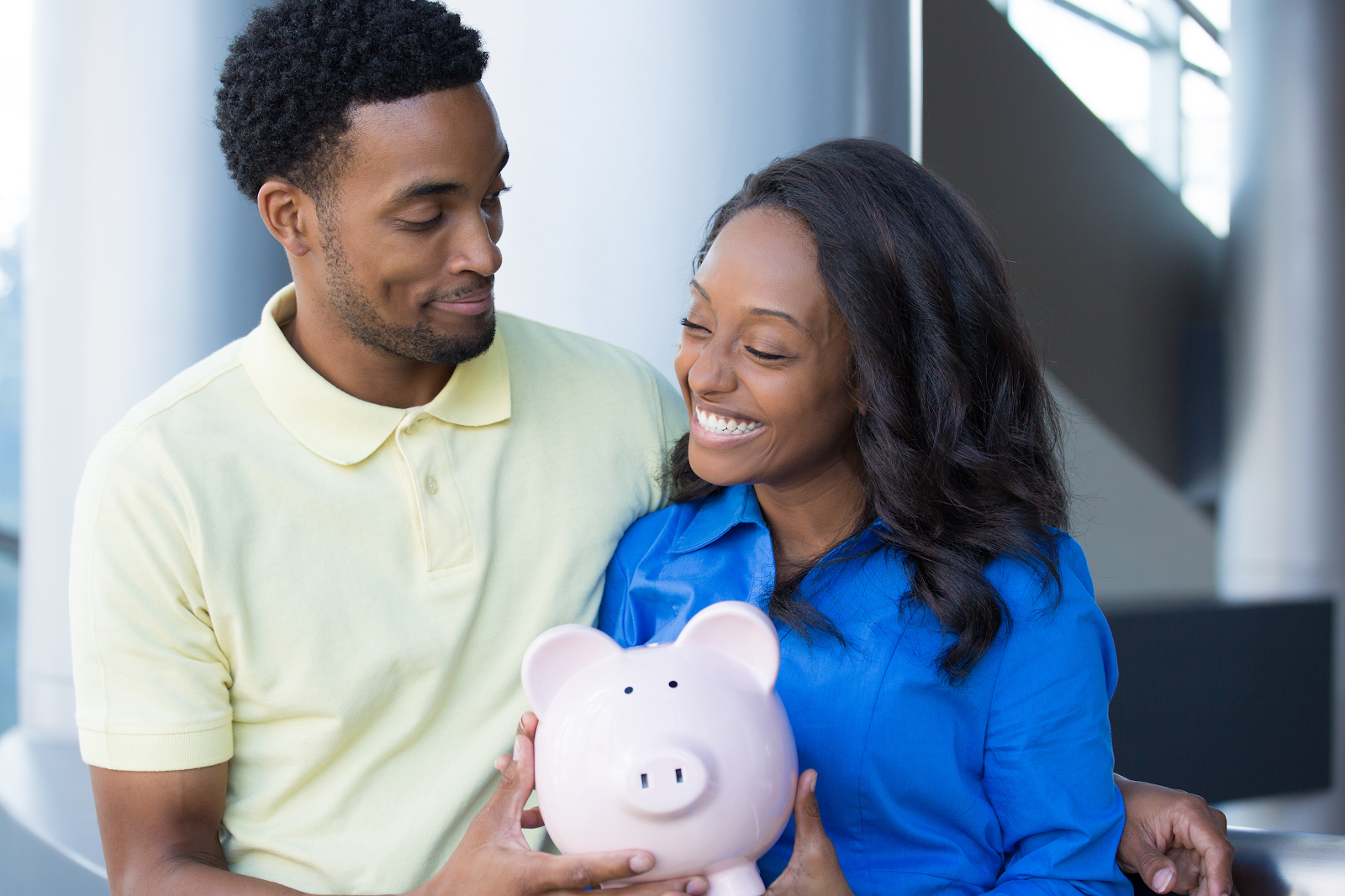 Co-borrowers holding a pink piggy bank together, symbolizing shared financial responsibilities