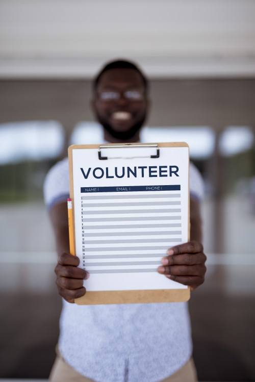 man, clipboard, sign, up, volunteer, outreach, checklist, holding, standing, outdoors, outside, writing, names, paper, board, list, contact, information, sheet, pencil