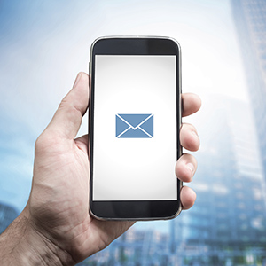 Hand holding mobile smart phone with message on a screen. E mail icon, Office buildings background