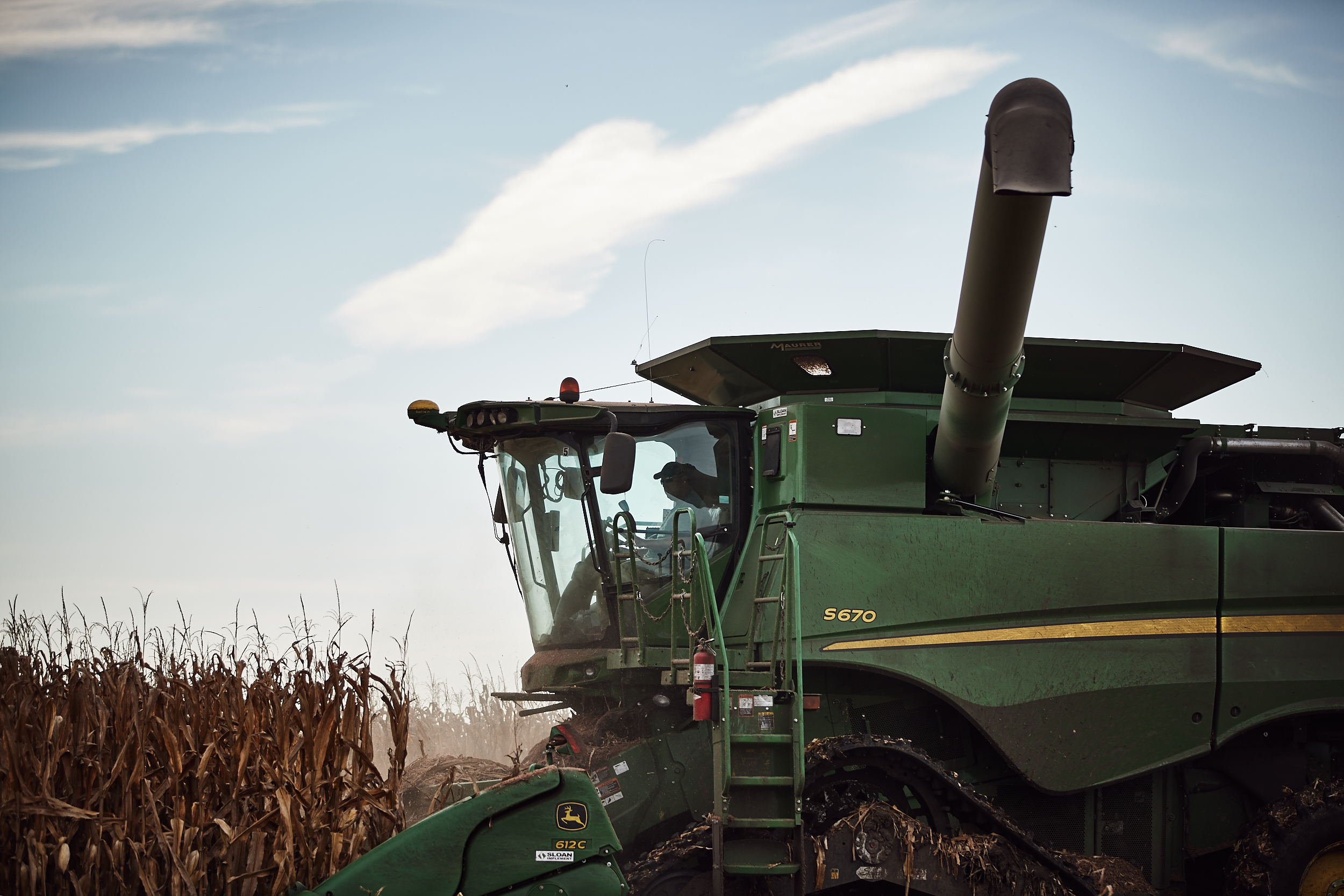 A harvester working in the corn field up close