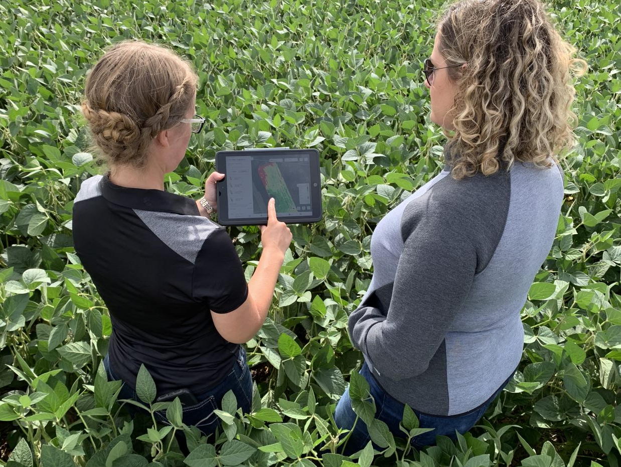 Two female farmers standing in the field looking at a field data report in Climate FieldView app on a tablet PC.